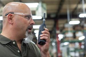 man in warehouse on two way radio