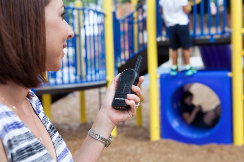 Teacher with two-way radio at school playground
