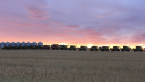 Farm machinery lined up on farm at sunset