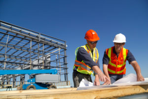 workers in hard hats communicate plans on construction site