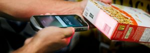 retail store employee scans box bar code with smartphone